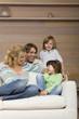 Familie sitzt auf dem Sofa, lächelnd, Porträt
