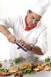 Koch würzt gegrillten Fisch