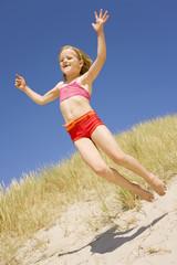 Deutschland, Ostsee, Mädchen springt von Sanddüne