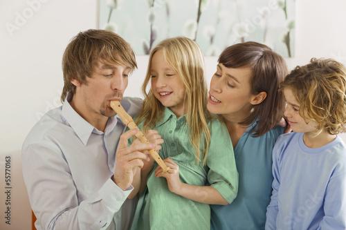 Familie im Wohnzimmer, der Vater spielt Blockflöte, Portrait