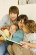 Familie beim Vorlesen im Wohnzimmer