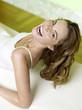 Frau liegt auf dem Bett und lacht, Porträt, erhöhte Ansicht