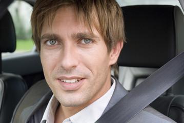 Junger Mann sitzt im Auto, Portrait