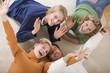 Familie auf dem Boden liegend im Wohnzimmer, lächelnd, erhöhte Ansicht