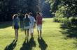Vier junge Menschen zu Fuß in Park, Rückansicht
