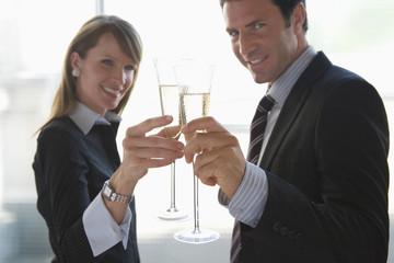 Geschäftsfrau und Geschäftsmann prosten sich zu