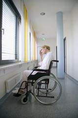 Frau sitzt in einem Rollstuhl