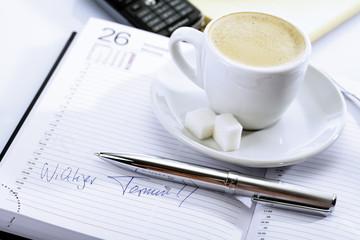 Tasse Kaffee auf einem Tagebuch, Kugelschreiber vor