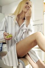 Junge Frau sitzt in der Küche, isst Trauben