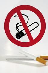 Zwei Zigaretten vor Rauchverbot Schild