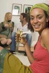 Junge Frau mit Sektglas, Paar im Hintergrund