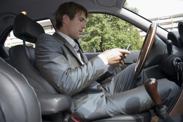 Junger Mann mit Handy, sitzend im Auto