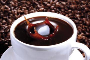 Zuckerwürfel fallen in Tasse Kaffee