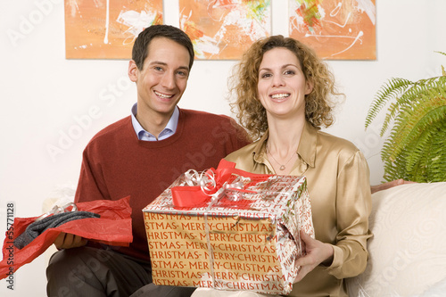 Paar sitzt auf dem Sofa, hält Weihnachtsgeschenke