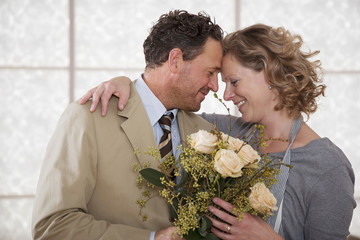 Älteres Paar in der Küche mit Blumenstrauß