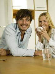 Junges Paar in der Küche, Frau hält Kaffeetasse, lächelnd