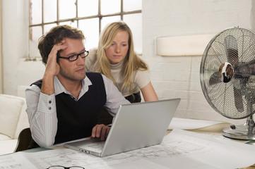 Junger Mann und junge Frau arbeiten am Laptop