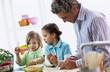 Vater mit Kindern macht Essen zu