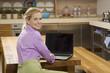 Junge Frau in der Küche, mit Laptop, lächelnd, Porträt