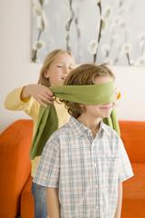 Junge und Mädchen spielen Blindekuh