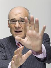 Älterer Geschäftsmann macht Stop-Geste, Portrait