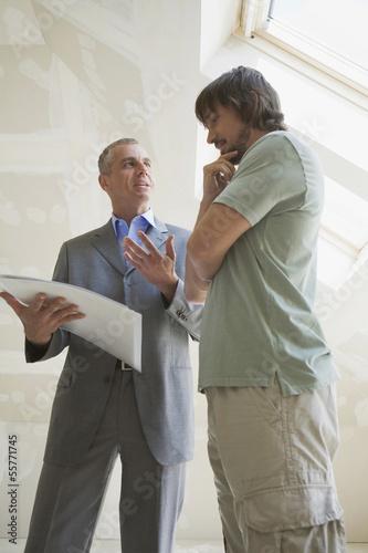 Zwei Männer schauen Bauplan an