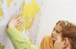 Jungen und Mädchen mit Blick auf Weltkarte