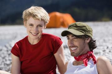Deutschland, Bayern, Tölzer Land, Junges Paar sitzt am Fluss, Portrait, Nahaufnahme