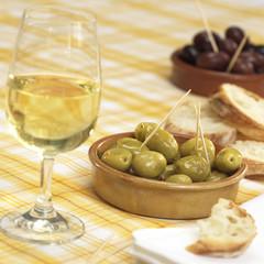 Glas Wein mit Oliven und Brot auf dem Tisch