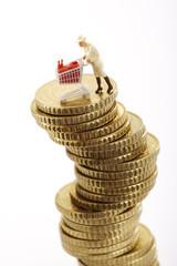 Figur mit Einkaufswagen auf Stapel von Münzen