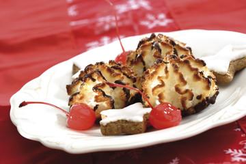 Kokos-Makronen und sternförmige Zimtkekse auf einem Teller