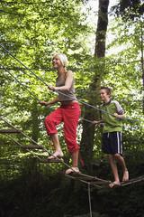 Teenager, Mädchen und Jungen zu Fuß auf Seilbrücke