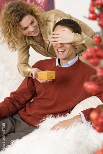 Frau hält ihrem Freund die Augen zu und überreicht ein Geschenk