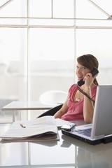 Frau am Schreibtisch mit Telefon