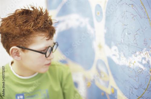 Junge mit Blick auf Weltkarte