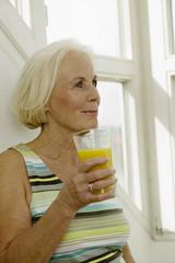 Seniorin mit Glas Saft, lächelnd, Nahaufnahme