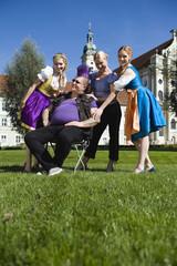 Deutschland, Bayern, Oberbayern, Frauen in traditionellen Kostümen und Mann mit Punk-Frisur
