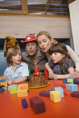 Familie bei Geburtstagsparty, Familie bläst Kerzen auf Torte aus, Portrait