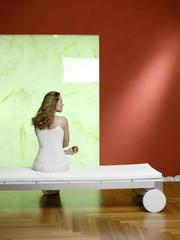 Frau mit Apfel sitzt auf dem Bett, Rückansicht