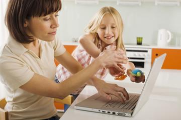Mutter und Tochter in der Küche, die Mutter mit Laptop