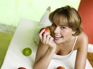 Frau liegt auf dem Bett mit Äpfeln, lächelnd