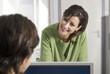 Geschäftsmann und Frau sprechen im Büro, lächelnd