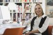 Geschäftsfrau im Büro hält Tasse, lächelnd, Porträt
