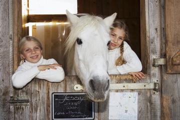Zwei Mädchen mit Pferd im Stall, Portrait