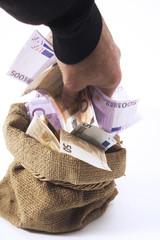 Mann nimmt Geld aus Sack