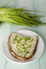 Brot und Butter auf Teller mit Schnittlauch