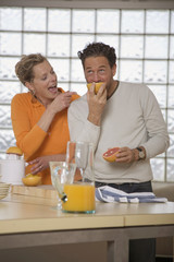 Älteres Paar in der Küche, Mann isst Grapefruit