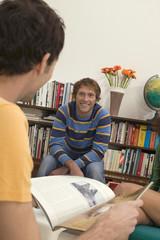 Zwei junge Männer, einer hält ein Magazin, Rückansicht