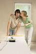 Junges Paar bei der Renovierung, Frau küsst Mann