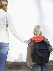 Junge zu Fuß unterwegs mit Mutter, Rückansicht